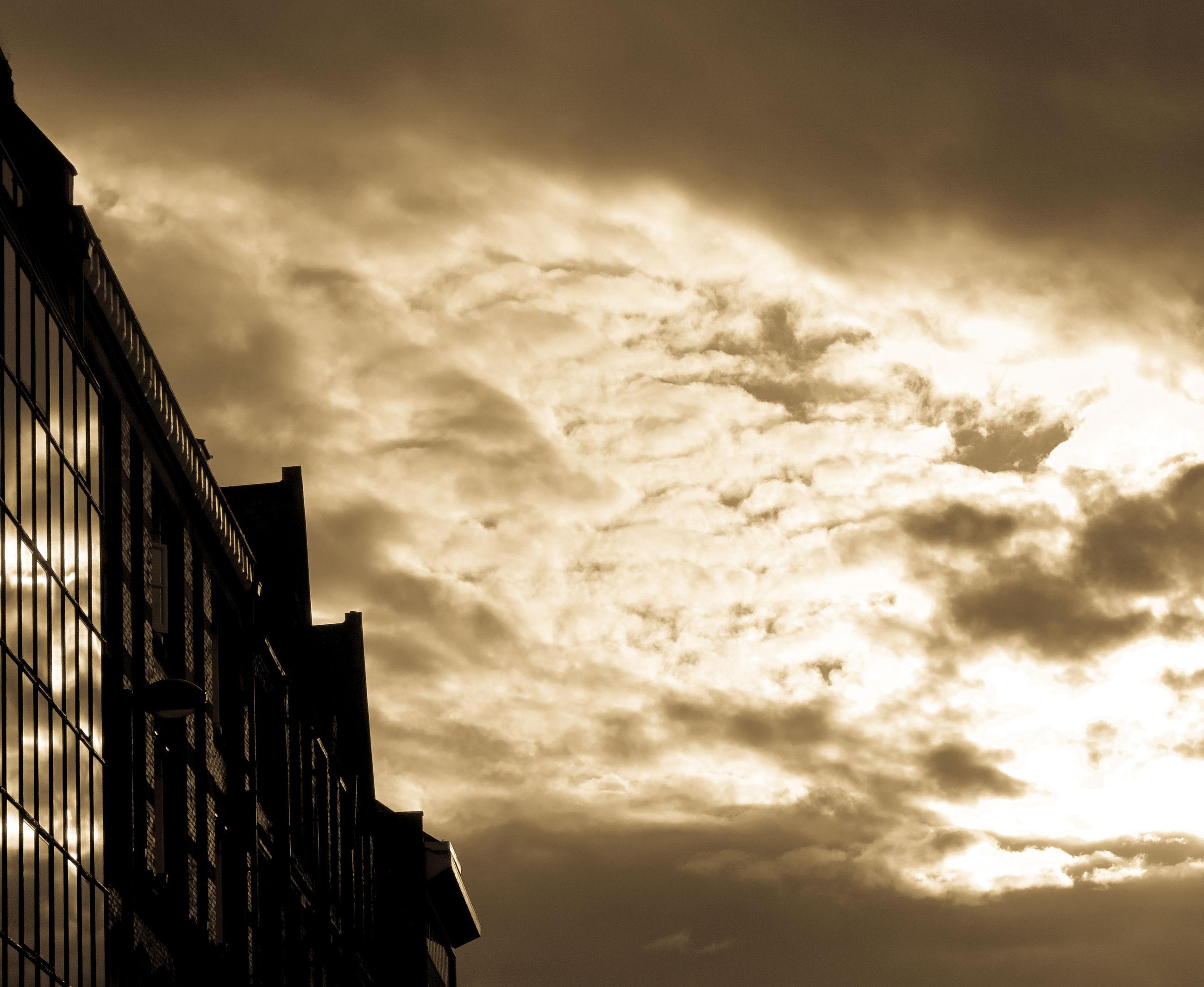 sky, architecture, building exterior, cloud - sky, built structure, cloudy, low angle view, cloud, sunset, building, weather, overcast, city, residential structure, residential building, outdoors, dramatic sky, no people, dusk, storm cloud