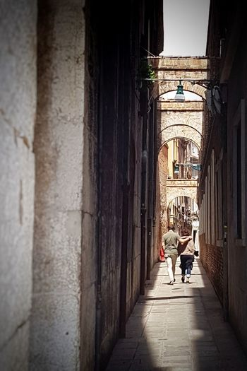Rear view of people walking in alley amidst buildings in city