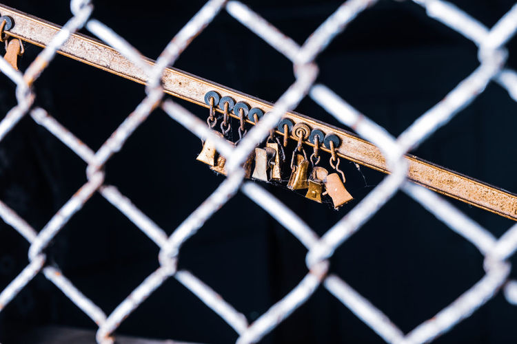 Rusty locks hanging on railing seen through chainlink fence against black background