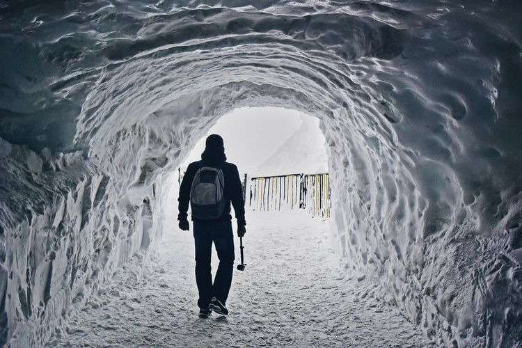 Rear view of man walking in ice cave