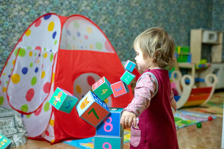 child little girl play with wooden cube toys at home or kindergarten Childhood Child One Person Toy Girls Innocence Lifestyles Leisure Activity Offspring Real People Boys Standing Multi Colored Casual Clothing Females Rear View Three Quarter Length Males  Hair Hairstyle