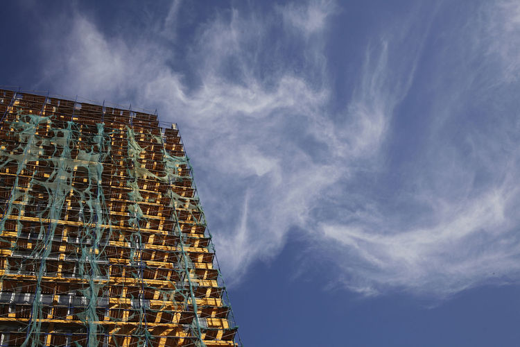 Low Angle View Of Building Covered With Scaffoldings Against Sky