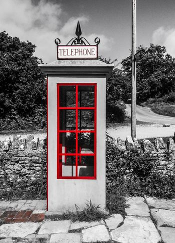 Old phone box in an abandoned village. EyeEmNewHere Telecommunications Technology Old Fashioned Vintage Dorset Tyneham Village Call Phone Communicate Wartime  Colour Pop Telephone Box British Old Phone Booth Old Phone Box Old Phone Communication Outdoors Text Telephone Booth Red Architecture No People Telephone Pay Phone Built Structure EyeEmNewHere