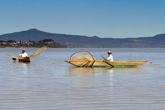 Fishermen on Lake Patzcuaro with traditional butterfly shaped nets and wooden boats Fisherman Fishing Fishing Net Hat Lake Lake Patzcuaro Mexico Michoacan, México Nautical Vessel Occupation Outdoors People Sky Travel Water
