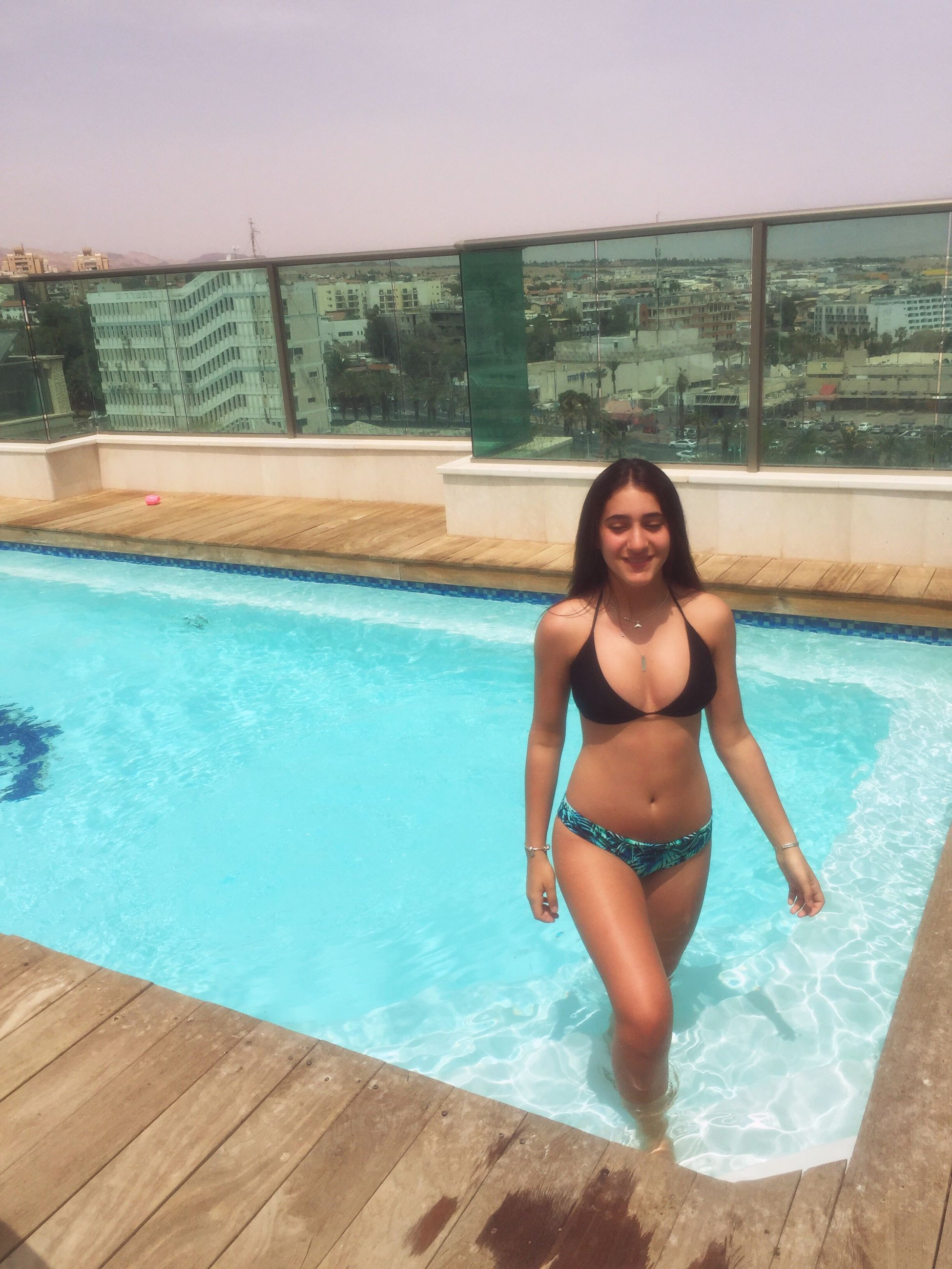 water, swimming pool, lifestyles, real people, standing, one person, vacations, young women, bikini, leisure activity, smiling, young adult, outdoors, beautiful woman, beauty, adult, only women, people, day, adults only