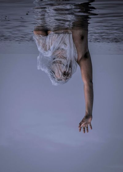 Upside down image of shirtless man with plastic covered face drowning in sea