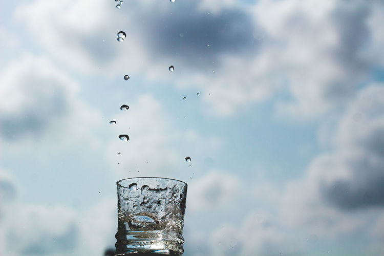 Close-up of water splashing on glass against sky