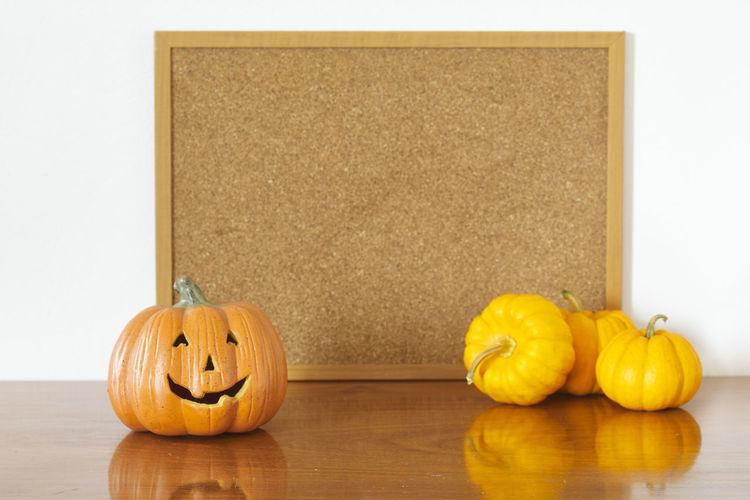 Jack o lantern and pumpkins against bulletin board on table