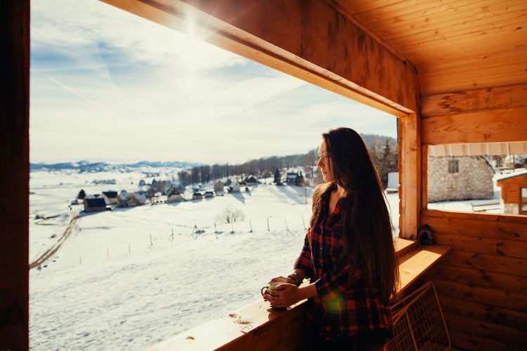Young woman holding cup while standing by window in cottage during winter