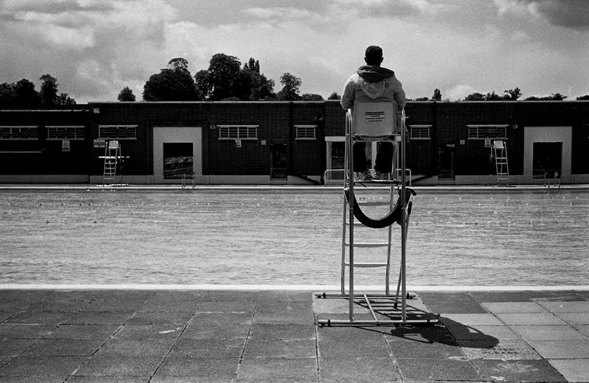 Lifeguard at the Lido City Life Day Full Length Incidental People International Landmark Leisure Activity Lifeguard London City Brockwell Lido Sat Chair Pool Water Save Lives Black & White Film Negative Documentary Reportage Street Photos Photography Clouds Sky Trees Park Swim Swimming Lifestyles Men Mode Of Transport Outdoors Real People Rear View Standing Sunlight, Shades And Shadows Tourism Transportation Urban Walking Women