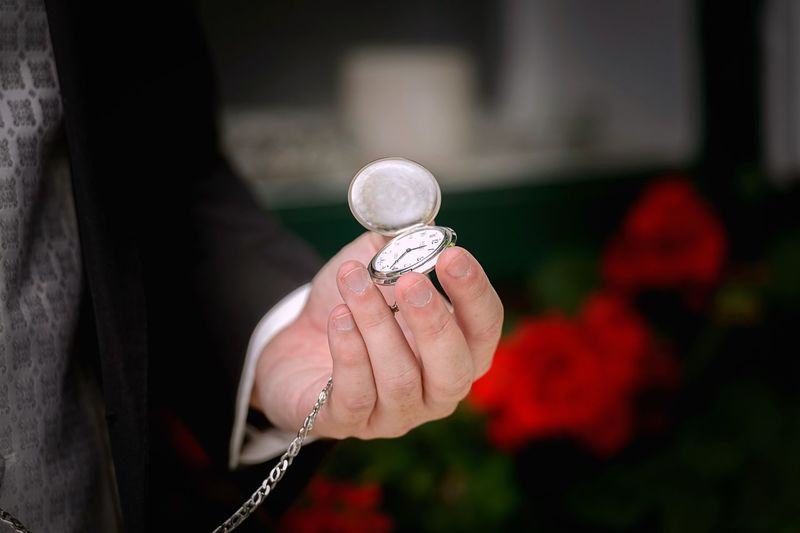 Midsection of person holding pocket watch at home