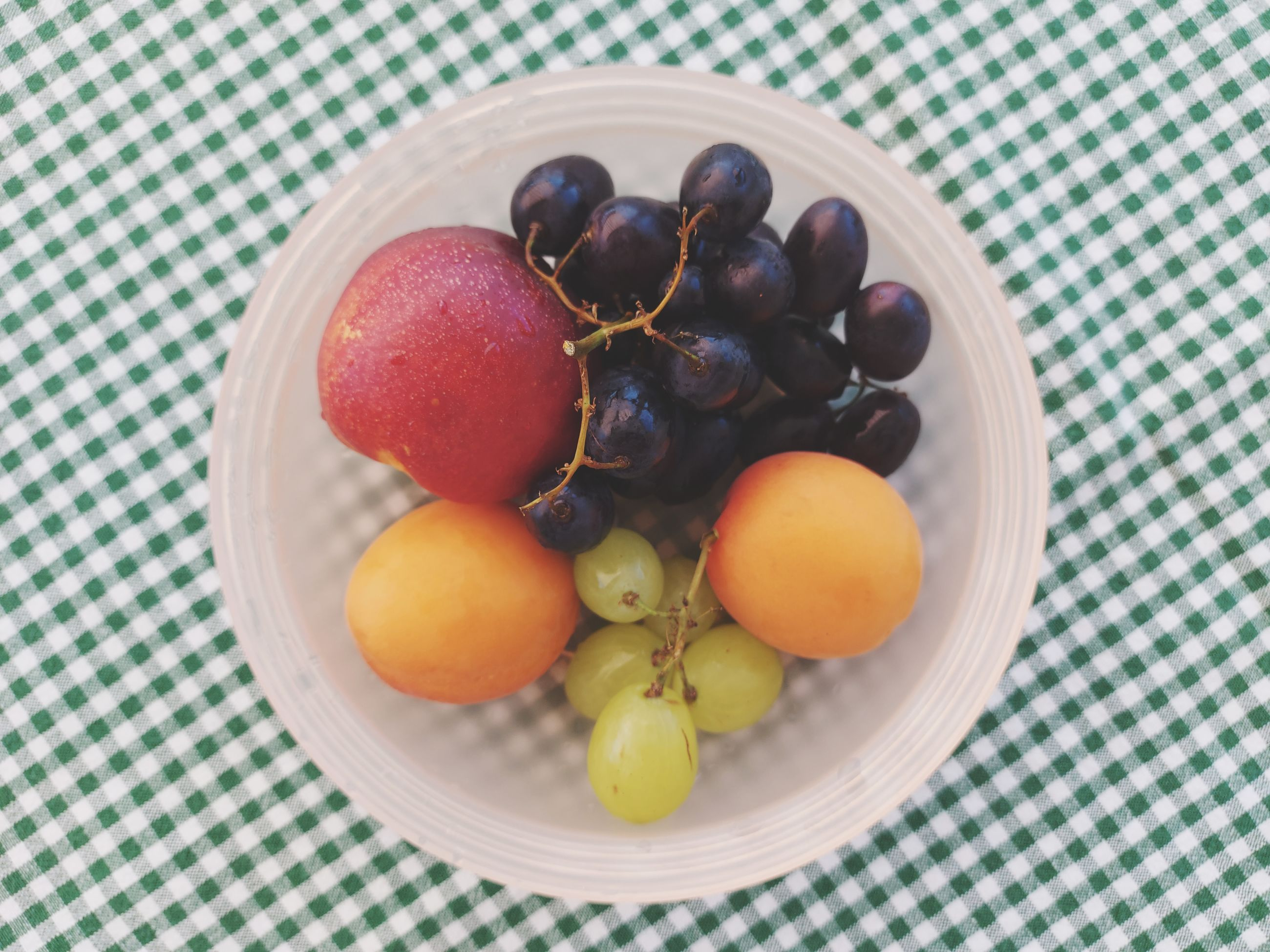 food, food and drink, healthy eating, fruit, wellbeing, freshness, plant, produce, tablecloth, bowl, no people, high angle view, indoors, directly above, still life, sweet food, grape, table, apricot, close-up, checked pattern, berry, plate