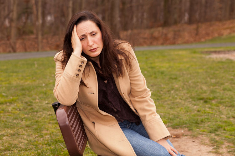 Thoughtful Woman Sitting On Bench In Park