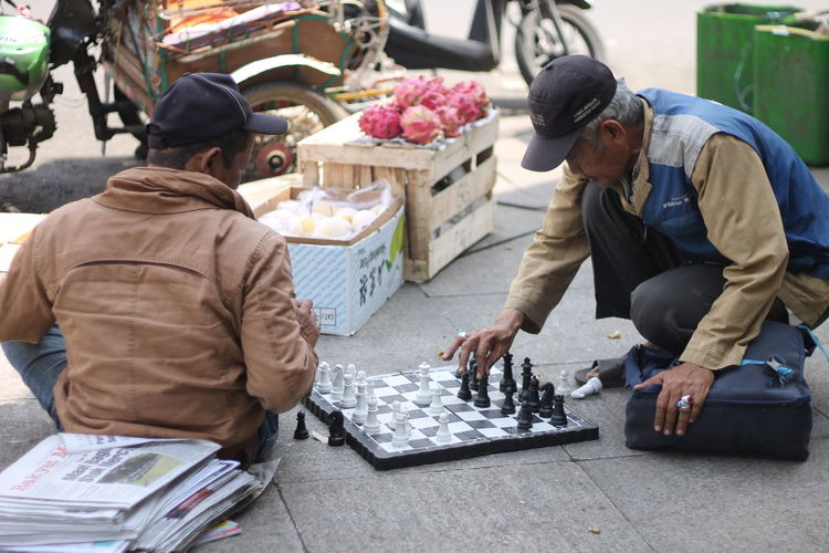 2 men playing chess in the street Streetphotography Street Photography Indonesia Street Photography 2 Man One Person Old Playing Chess Playing Chess In The Street Men Men Playing Chess Concentration Two People Bandung Habit Cultures Males  Sitting