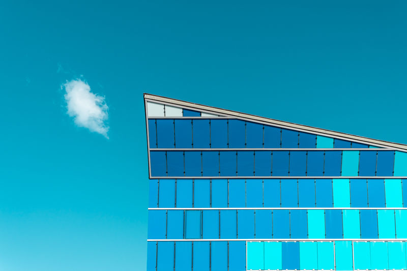 Scenic View Of Glass Building Against Cloudy Sky