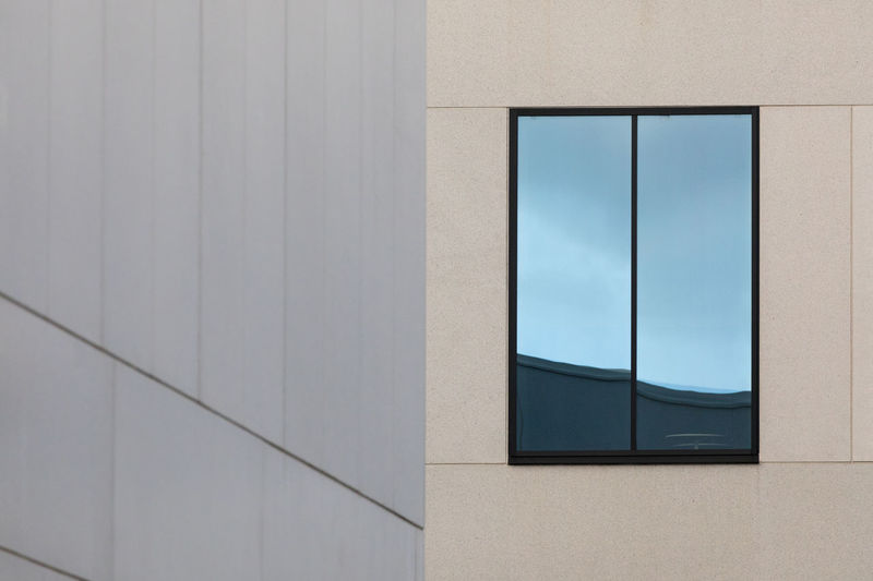 Close-up of a reflective window and grey wall of another building in the foreground City Copy Space Low Angle View Modern Reflection Architecture Backgrounds Building Exterior Built Structure Close-up Concrete Day Focus On Background Full Frame Geometric Shape Glass - Material No People Office Building Exterior Outdoors Pattern Rectangle Simplicity Single Object Wall - Building Feature Window