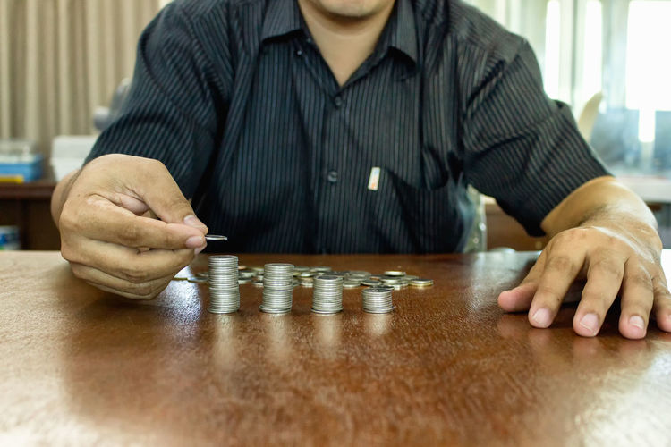 Midsection of man stacking coins on table