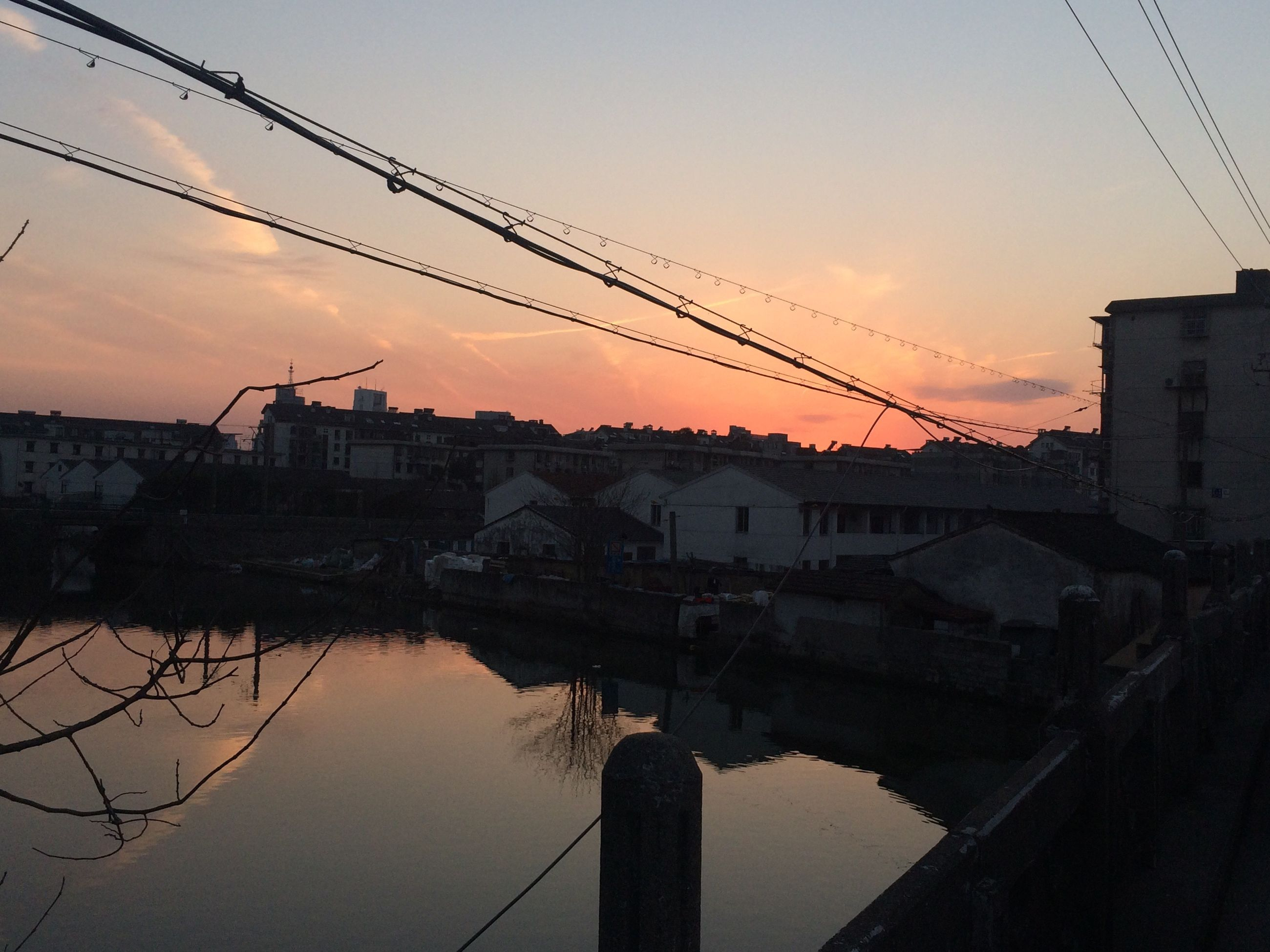 architecture, built structure, building exterior, sunset, water, sky, connection, power line, silhouette, electricity pylon, reflection, river, house, city, cable, residential structure, outdoors, residential building, no people, orange color