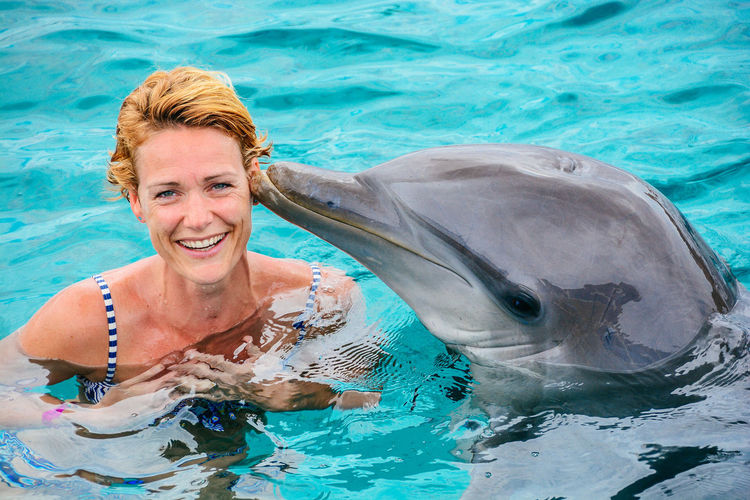 Portrait of smiling woman with dolphin swimming in sea