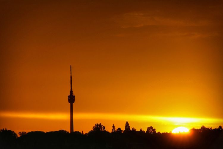 Silhouette of communications tower in city during sunset