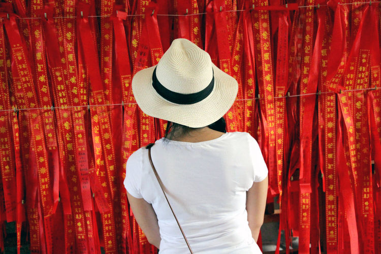 Rear View Of Woman Standing Against Red Ribbons For Sale In Market