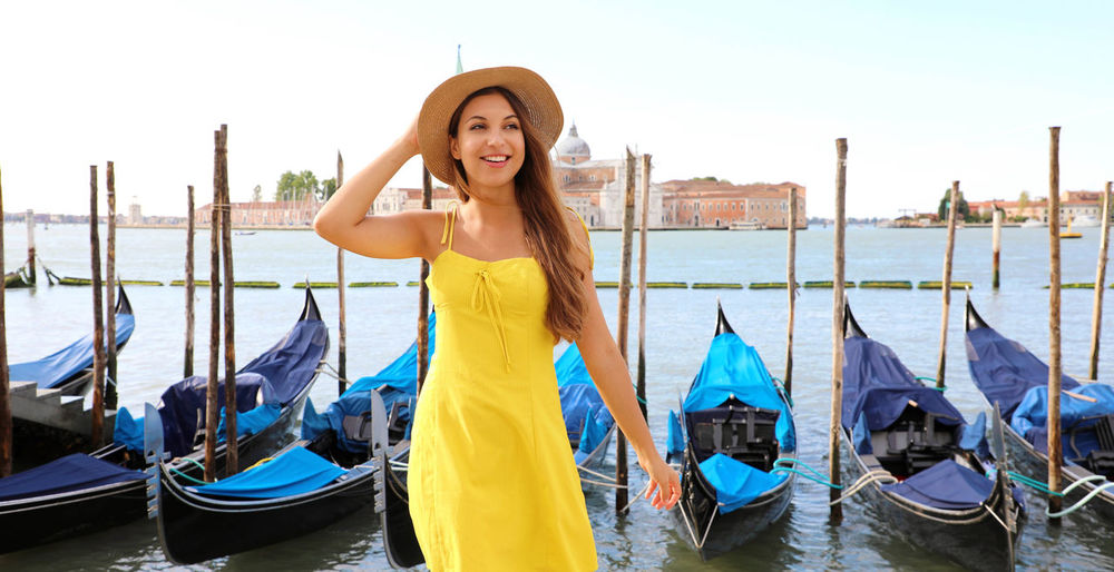 Portrait of happy young woman in boat against canal