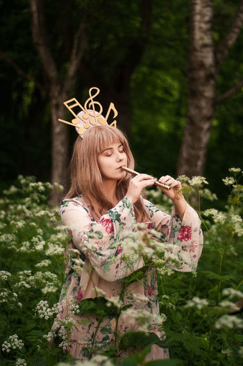 Young Woman With Eyes Closed Playing Flute While Standing In Forest