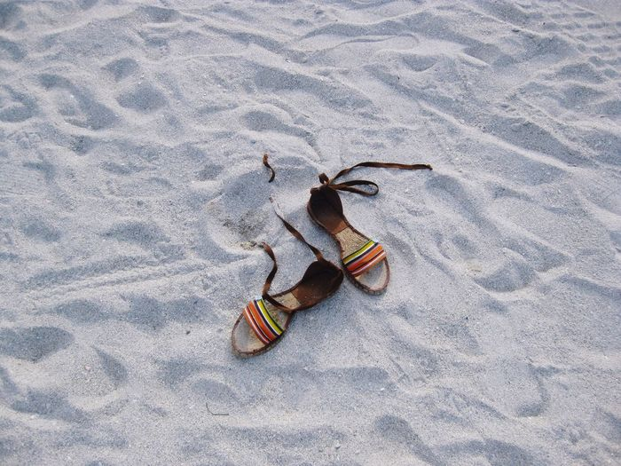High Angle View Of Footwear On Sand At Beach