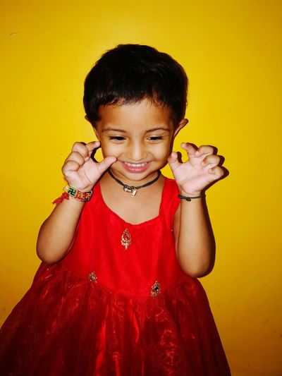 Smiling Girl Gesturing While Standing Against Yellow Background