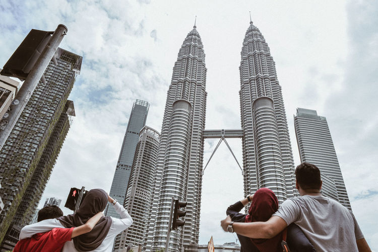 Rear view of people looking at petronas towers against cloudy sky
