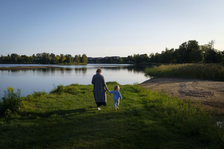 Rear view of mother and daughter walking by lake against sky