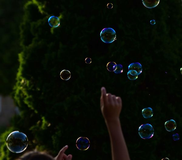 Cropped arm raised amidst bubbles in mid-air