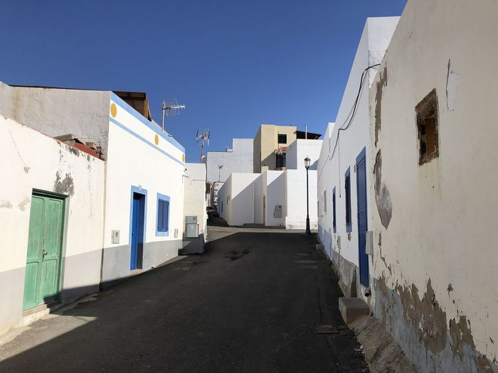 Alley amidst buildings against blue sky