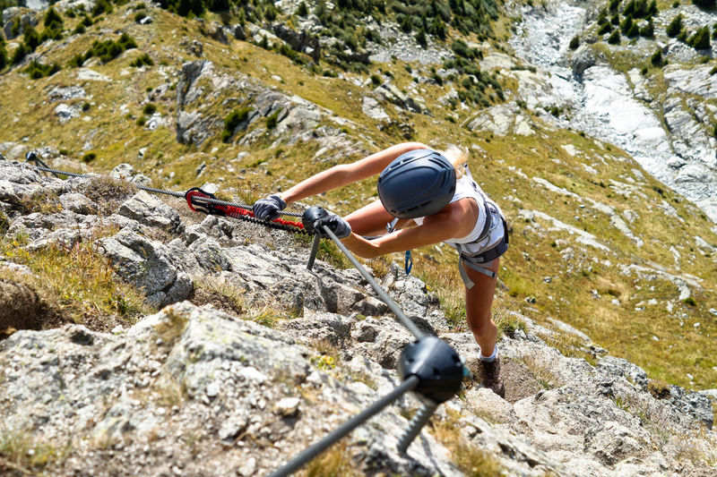 Full length of woman climbing rocks in a mountain at heini-holzer-klettersteig