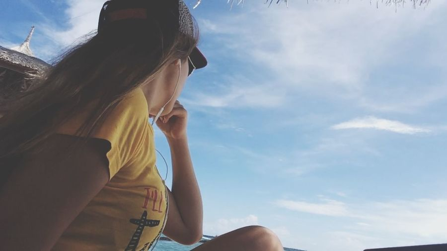 Woman sitting outdoors looking at sky