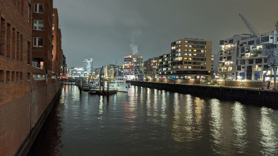 River amidst illuminated buildings in city at night