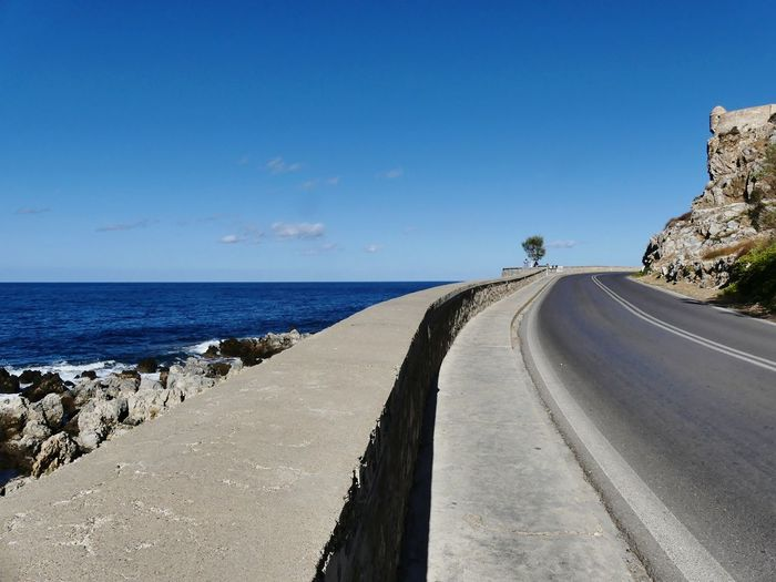 Panoramic view of road by sea against blue sky