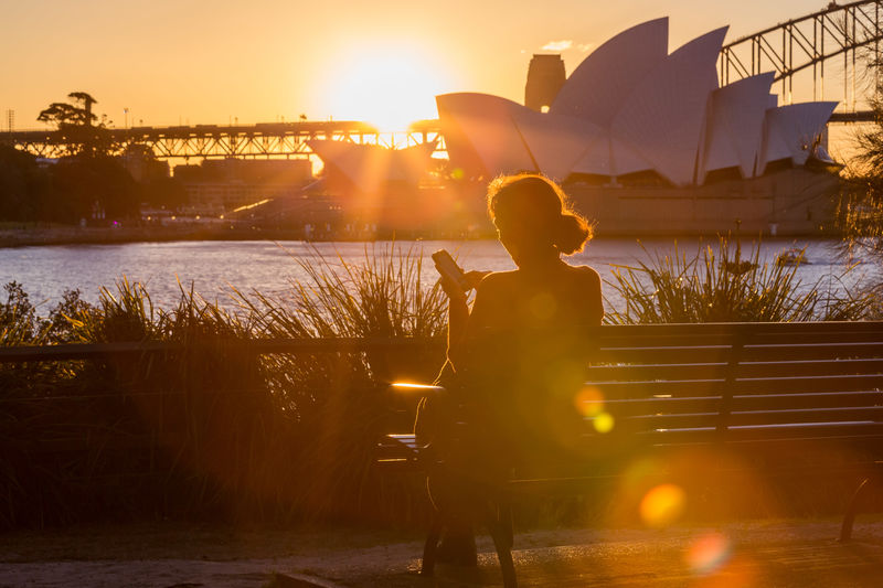 A lone woman sits on a park bench in the late afternoon sun using her phone with the Sydney Harbour Bridge and Sydney Opera House in the background. Afternoon Australia Holiday Peace Quiet Moments Relaxing Serenity Sydney Harbour Bridge Sydney Opera House Sydney Harbour  Travel Woman Architecture Australian Landscapes Destination Into The Light Into The Sun Lens Flare Phone Seat Sunset Texting Unidentified Person Warm Water