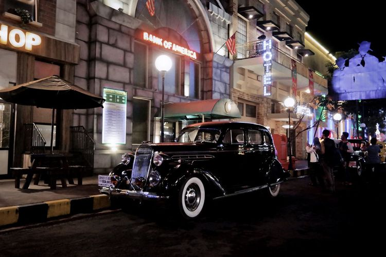 Vintage car on illuminated city at night