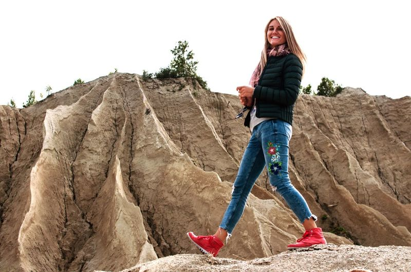 Full Length Portrait Of Smiling Young Woman Walking Against Rock Formation