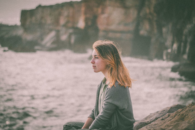 Thoughtful woman looking away against rock formation
