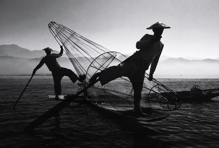 Low angle view of man fishing in sea against sky