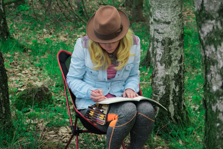 Young woman drawing in book by tree trunk