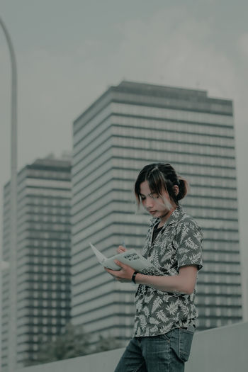 Young woman using mobile phone standing against building