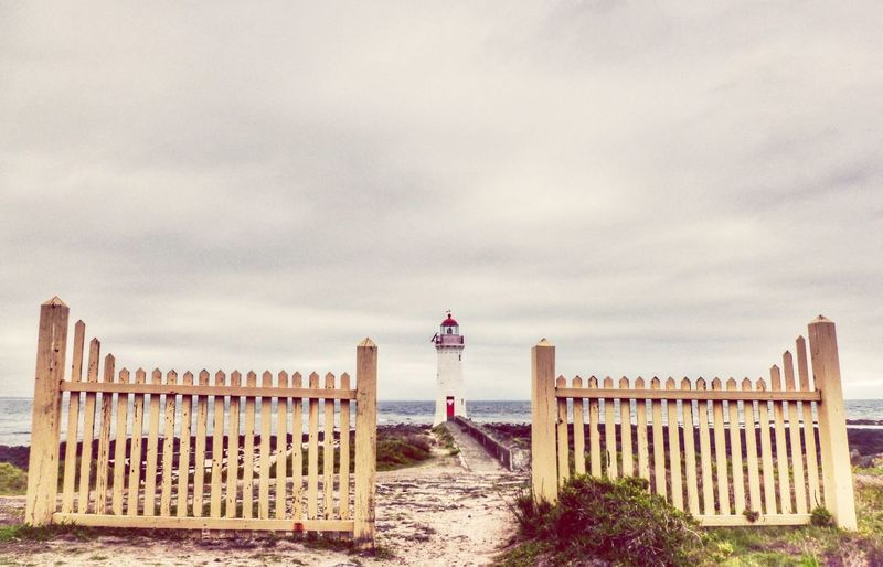Lighthouse on shore against cloudy sky