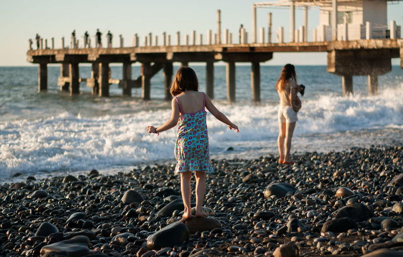 Mother with child girl at the sea beach on sunset
