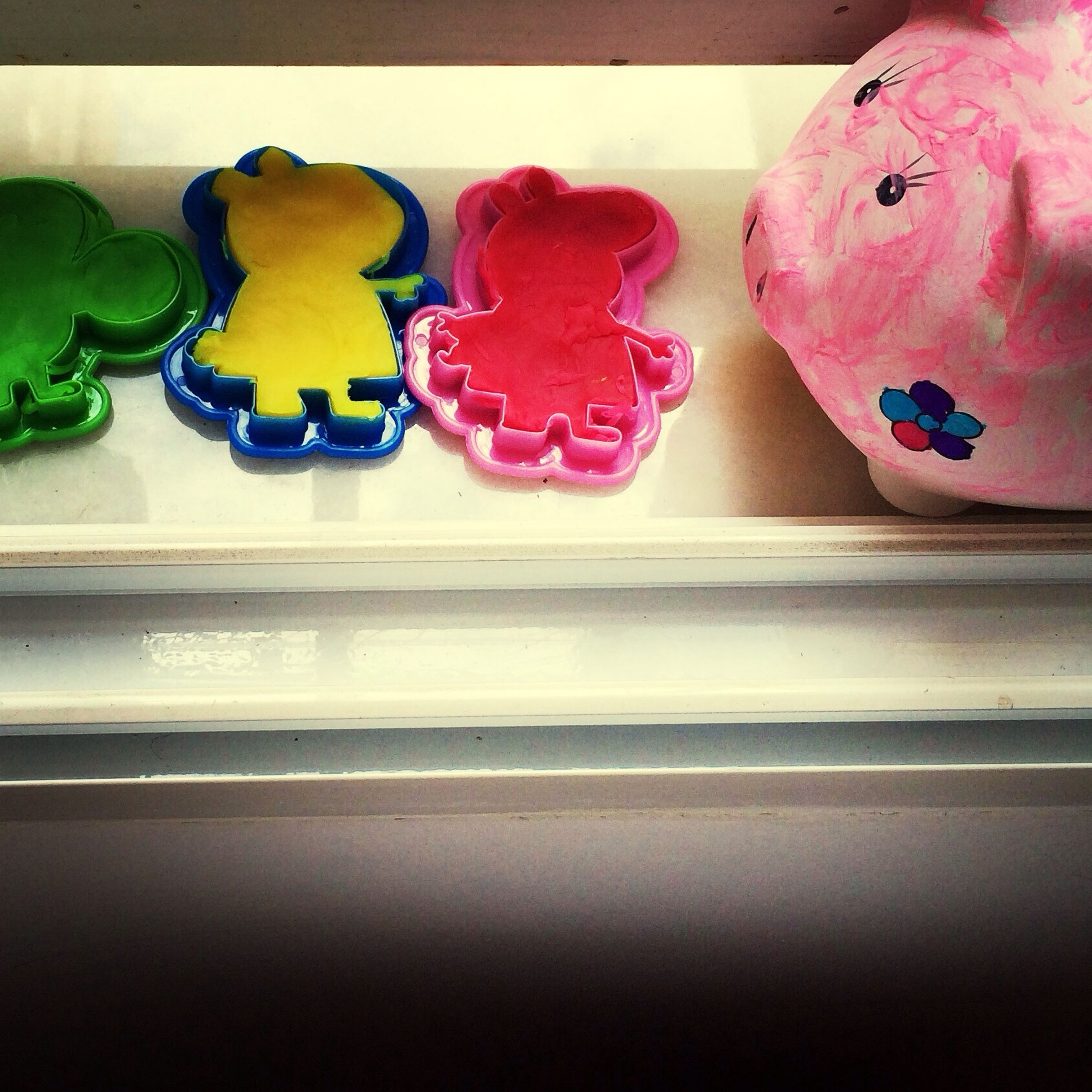 indoors, multi colored, animal representation, art and craft, art, still life, creativity, toy, human representation, variation, close-up, high angle view, red, no people, childhood, decoration, pink color, table, freshness, wall - building feature