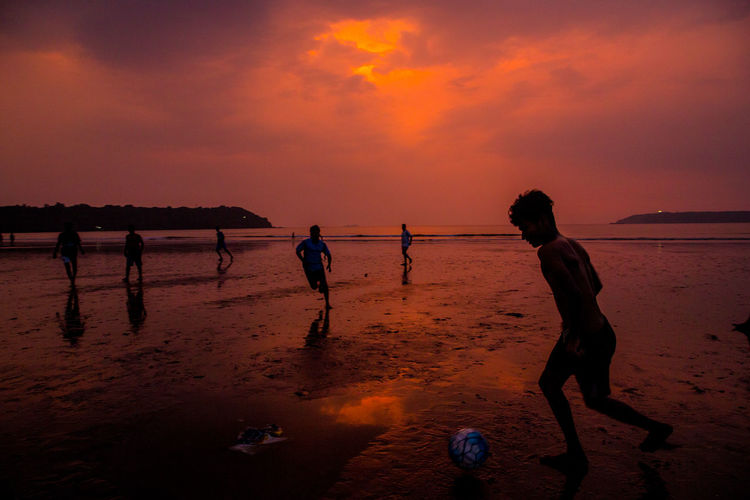 Beach Beach Volleyball Beauty In Nature Horizon Over Water Leisure Activity Lifestyles Men Nature Orange Color Outdoors People Playing Real People Sand Scenics Sea Shore Silhouette Sky Sport Sunset Vacations Water