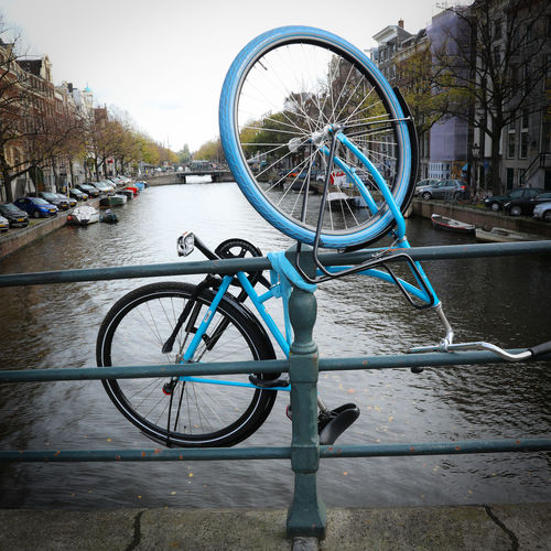 Bicycle parked on street by river in city