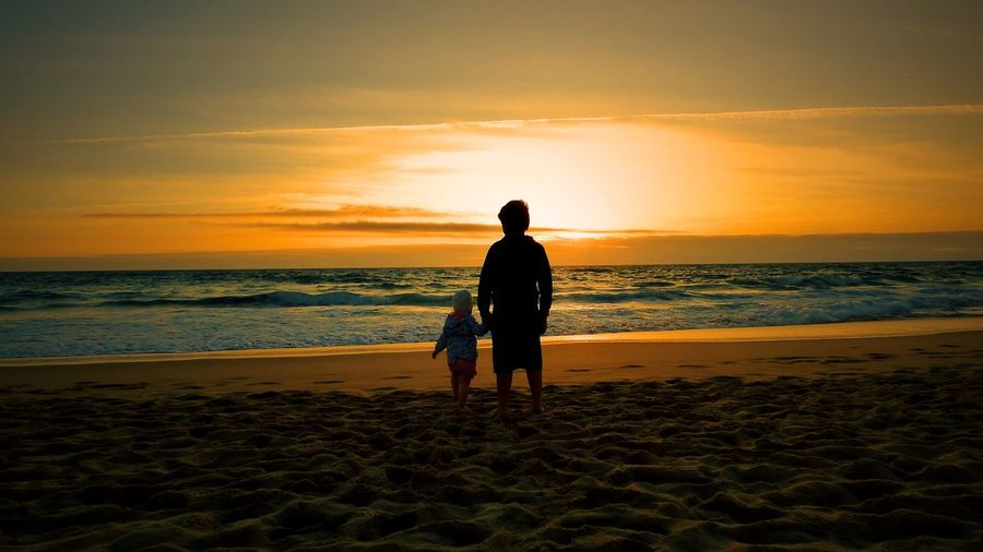 Silhouette Man With Son Standing On Sandy Beach During Sunset